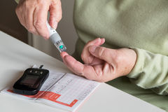 Diabetes self test of blood sugar with glycometer. Woman testing blood sugar by pricking finger with specialist home equipment, and recording result in log book Royalty Free Stock Photography