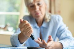 Senior Woman Testing Blood Sugar Level At Home. Senior Woman Tests Blood Sugar Level At Home stock photography
