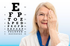 Senior woman testing vision with eye chart. Close up portrait of senior woman testing vision Woman closing one eye with hand.Alphabet test chart with focus point Stock Photography