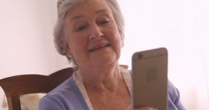 Senior woman text messaging on mobile phone. At home stock footage