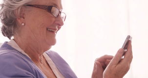 Senior woman text messaging on mobile phone. Smiling senior woman text messaging on mobile phone at home stock footage