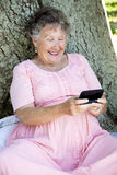 Senior Woman Texting. Senior woman outdoors, texting on her smart phone Stock Images