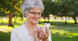 Senior woman texting on smartphone outdoors Stock Photo