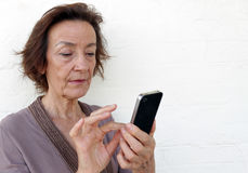 Senior woman texting. Senior woman using a smartphone to check her social media or text Stock Image