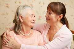Senior woman with their caregiver at home. Royalty Free Stock Image
