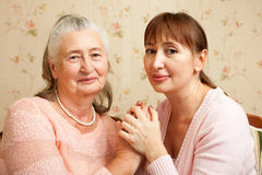 Senior woman with their caregiver at home. Royalty Free Stock Photography