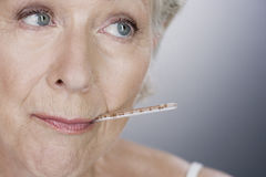 A senior woman with a thermometer in her mouth Stock Images