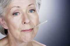 A senior woman with a thermometer in her mouth Royalty Free Stock Images