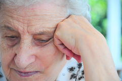 Senior woman thinking. Thouthful senior woman leaning on her hand Stock Images