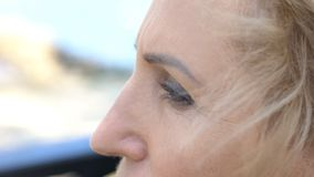 Senior woman thoughtfully looking in distance, face close-up, nostalgic memories royalty free stock image