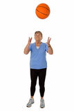 Senior woman throwing basketball Stock Images