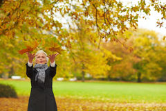 Senior woman throwing maple leaves. Senior citizen strolling in a park in autumn Royalty Free Stock Photography