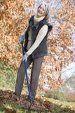 Senior woman tidying autumn leaves