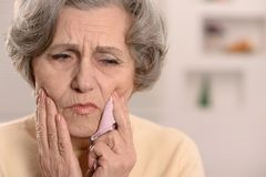 Senior woman with tooth pain. Elderly nice woman having bad tooth pain stock image