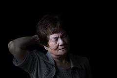 Senior woman touching the back of her head while in pain on blac Royalty Free Stock Photos