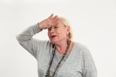 Senior woman touching her forehead. Royalty Free Stock Images
