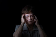 Senior woman touching her head while in pain on black background Stock Image
