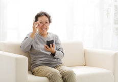 Senior woman touching the smart phone Stock Image