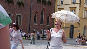 Senior woman tour guide with umbrella tell for tourists about old medieval european city. WROCLAW, POLAND - AUGUST, 2019. Senior woman tour guide with umbrella stock video footage
