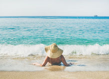 Senior woman tourist in bikini lying on sand enjoying sea. Beautiful slim senior woman tourist in bikini and hat lying on sand enjoying sea at Meditteranean Stock Photo