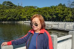 Senior women tourist stand beside the Lake on top of the xiqiao mountain foshan city china. Senior woman tourist stand beside the Lake on top of the xiqiao royalty free stock photos
