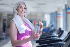 Senior woman with towel and water at gym. All you need. Smiling pretty senior woman covered with towel holding water bottle on race track at gym Stock Photos