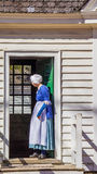Senior woman in traditional blue dress. Senior woman in Colonial Williamsburg in traditional english blue dress standing in doorway Stock Image