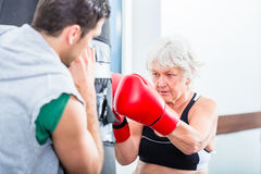 Senior woman with trainer in boxing sparring Royalty Free Stock Photography