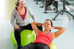 Senior woman with trainer exercising fitness ball. Fitness center senior women with trainer exercising on swiss ball Stock Images