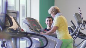Granny trains on the treadmill in the gym with trainer. Senior woman is training her legs in the gym on the treadmill. Trainer stands near granny and controls stock footage
