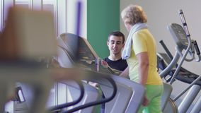 Elderly woman walks on treadmill in the gym. Senior woman is training her legs in the gym on the treadmill. Trainer stands near granny and controls process of stock footage