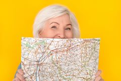 Senior woman traveler studio isolated on yellow wall covering face with map playful stock photo