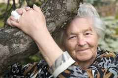 Senior woman by the tree Stock Images