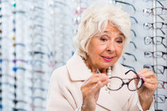 Senior woman trying on eyeglasses stock photo