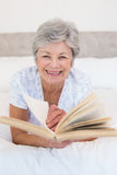 Senior woman turning story book pages Royalty Free Stock Photos