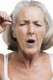Senior woman tweezing eyebrows against white background Stock Photos
