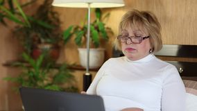 Senior woman types text using laptop. Woman with notebook stock footage