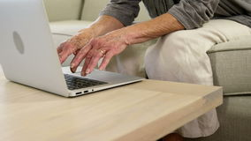 Senior woman typing on her computer. At home stock footage
