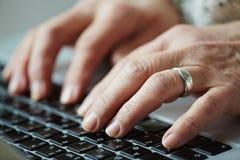 Senior woman typing on keyboard stock images