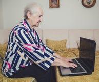 Senior woman typing on laptop Royalty Free Stock Photos