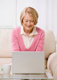 Senior woman typing on laptop on sofa. Stock Photos