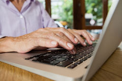 Senior woman typing on laptop at table in cafe shop Stock Image