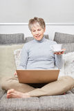 Senior woman uses laptop with relaxation Royalty Free Stock Photography