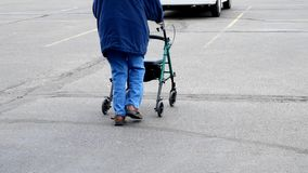 Senior woman uses a walker while walking outside on a parking lot. Senior woman uses a walker for assistance while walking outside on a parking lot stock video