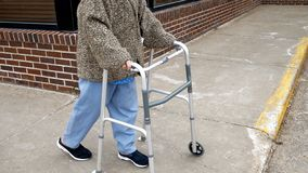 Senior woman uses a walker while walking on a sidewalk stock photos
