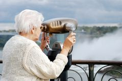 Senior woman using binoculars at niagara falls. Closeup of a senior woman tourist using binoculars at niagara falls royalty free stock image