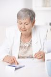 Senior woman using calculator Stock Photo