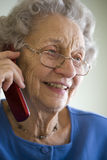 Senior woman using cell phone. Smiling elderly woman talking on cell phone Royalty Free Stock Photos
