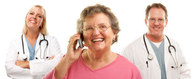 Senior Woman Using Cell Phone and Doctors Behind. Happy Senior Woman Using Cell Phone with Male and Female Doctors or Nurses Behind Isolated on a White Stock Images