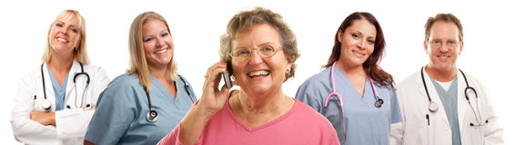 Senior Woman Using Cell Phone and Doctors Behind. Happy Senior Woman Using Cell Phone with Male and Female Doctors or Nurses Behind Isolated on a White Stock Image